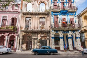 Vintage car parked in front of old buildings in Havana.