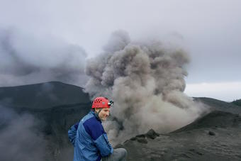 National Geographic photographer Carsten Peter stands near a volcano erupting smoke and steam.