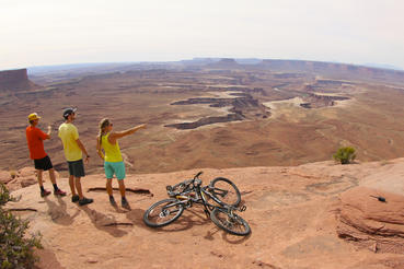 Conrad Anker, Max Lowe and Rachel Pohl overlook Canyonlands National Park while mountain biking through Moab, Utah.  Courtesy of MacGillivray Freeman Films. Photographer: Barbara MacGillivray