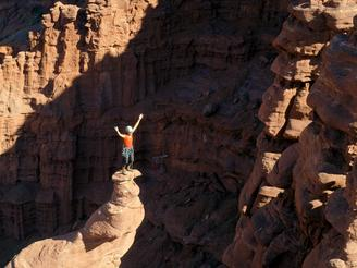 Climber Miranda Oakley stands atop the famous corkscrew summit on Ancient Art at Fisher Towers in Moan, Utah.