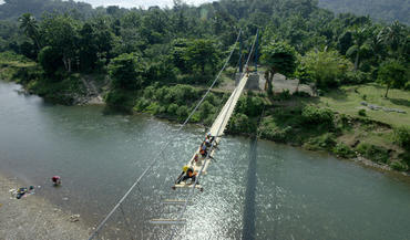 Engineers led by Avery Bang work on the new Chameau footbridge in Haiti. Bridges like these, built in developing countries, signal a new field of study and work called humanitarian engineering.