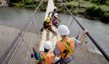 Engineers work on the final pieces of the Chameau footbridge in Haiti. The Chameau Bridge will provide much-needed access to schools and medical care for isolated, rural families.