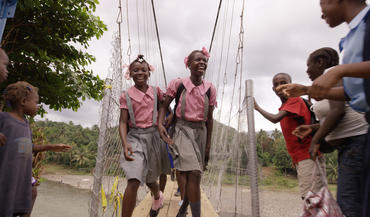 Haitian schoolgirls are among the first to walk across the newly built Chameau Bridge in Haiti. The bridge was built by the non-profit group Bridges to Prosperity, led by Avery Bang, which brings the benefits of engineering to developing countries.