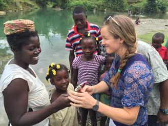 Engineer Avery Bang celebrates with local Haitian families who will benefit from the new Chameau Bridge. Avery is the head of the non-profit group Bridges to Prosperity, which has built more than 200 bridges in impoverished countries.