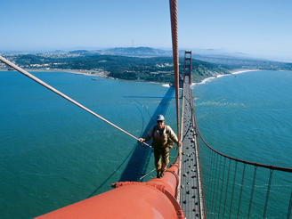 An engineer performs a routine inspection of the Golden Gate Bridge in San Francisco, California. The Golden Gate is a suspension bridge designed by a team of engineers in the 1930s. Up until 1964, it was the longest suspension bridge in the world.