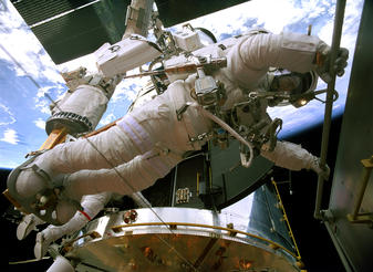 STS-125 astronaut Andrew Feustel transfers the Corrective Optics Space Telescope Axial Replacement unit (COSTAR) from the Hubble Space Telescope to its temporary stowage position in the Space Shuttle Atlantis cargo bay.