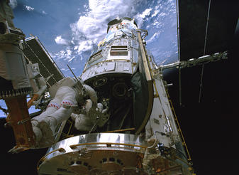 Astronaut Michael Good (on the Shuttle's remote manipulator arm) assists astronaut Michael Massimino into foot restraints to position him inside the Hubble Space Telescope without disturbing sensitive instruments he must work around.astronaut Michael Good (on the Shuttle's remote manipulator arm) assists astronaut Michael Massimino into foot restraints to position him inside the Hubble Space Telescope without disturbing sensitive instruments he must work around.