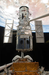 After completion of the final repairs, the Space Shuttle Atlantis' remote manipulator system arm lifts the Hubble Space Telescope from the cargo bay and is moments away from releasing the orbital observatory.