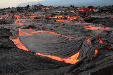 A mass of molten lava oozes from an erupting vent.