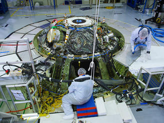 Engineers work on the finishing touches of Orion, before its first test launch in late 2014.